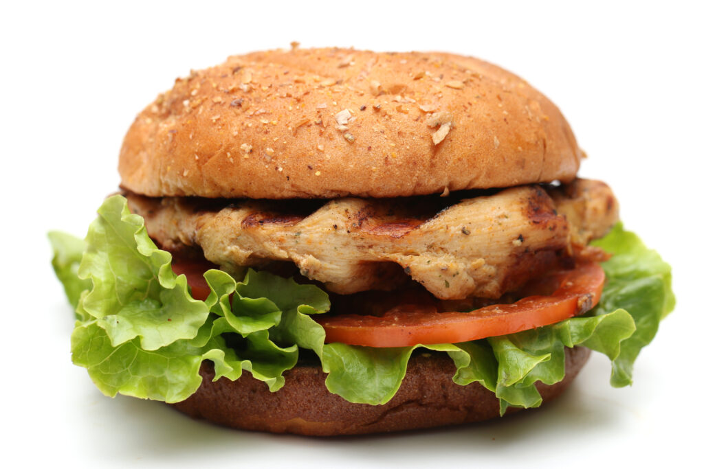Grilled chicken breast sandwich on whole grain bun with lettuce and tomato