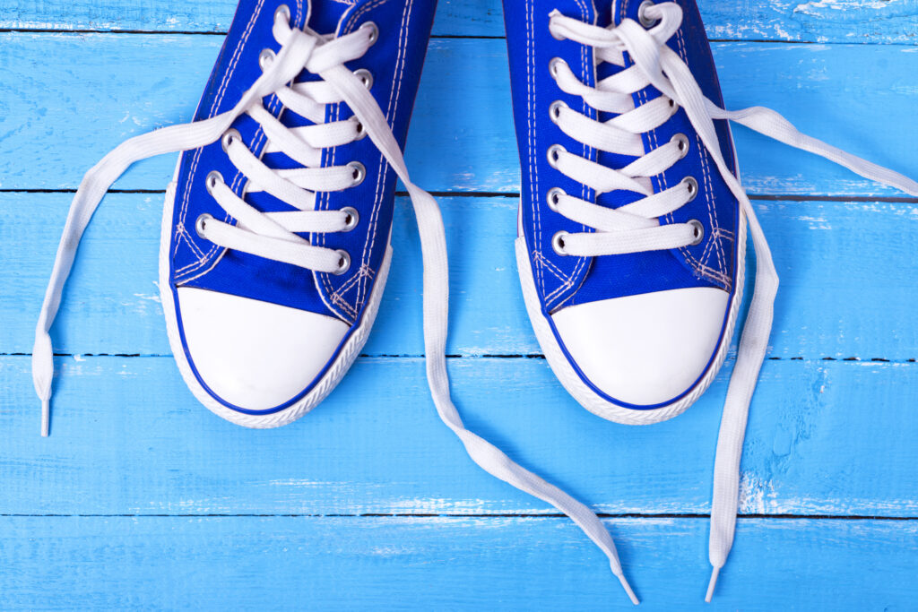 pair of blue canvas basketball shoes with loose white laces on a blue wooden background, top view