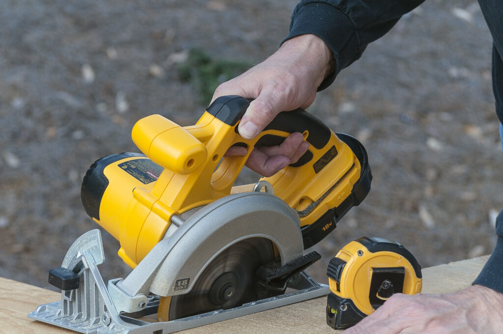 Yellow and gray circular saw operated by a right hand, with a yellow and black tape measure on the board beside it.