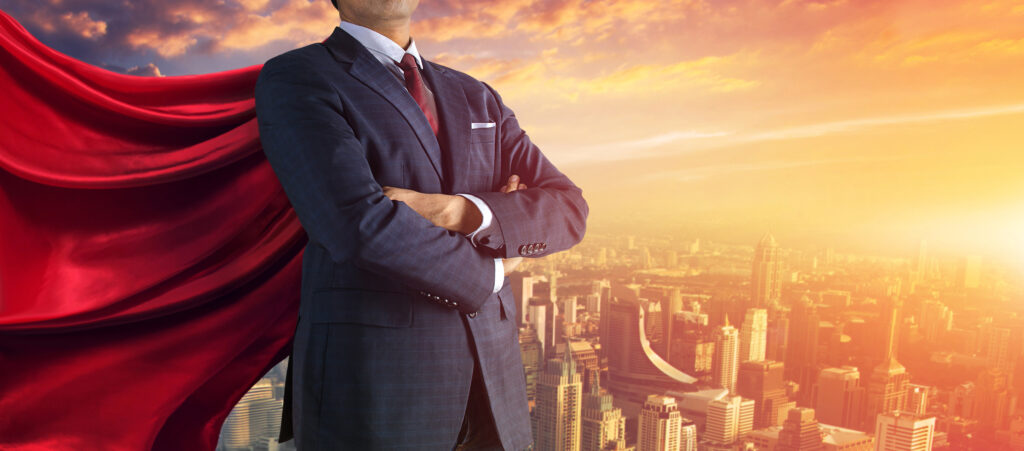 Image of an executive in a business suit with a hero's cape, against the hazy backdrop of a city. Photo shows only the man's torso.
